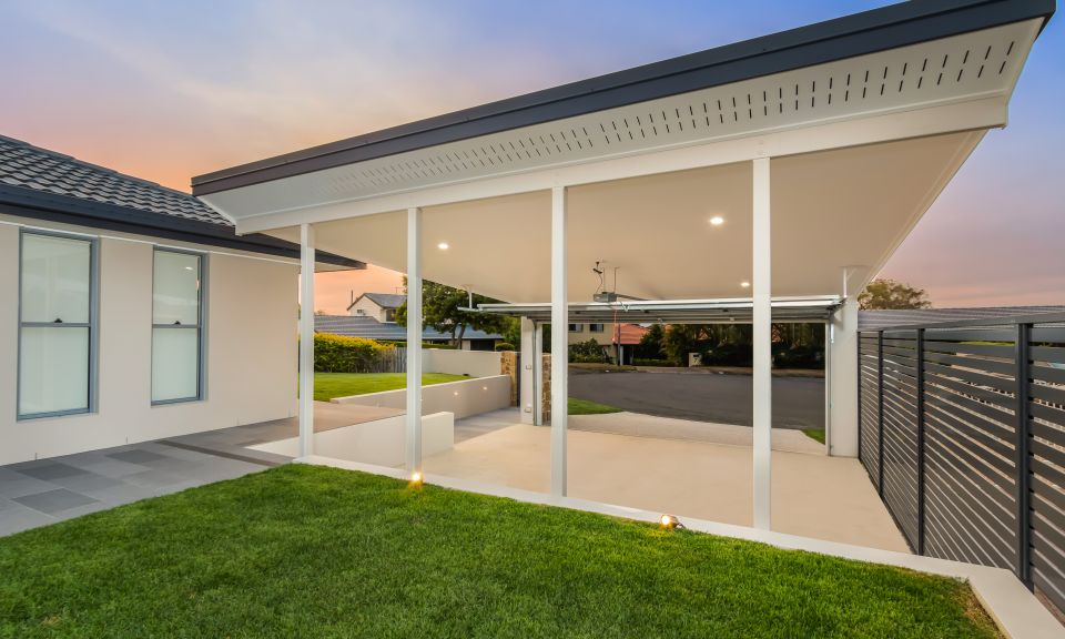 Double carport and front entry, exposed concrete driveway