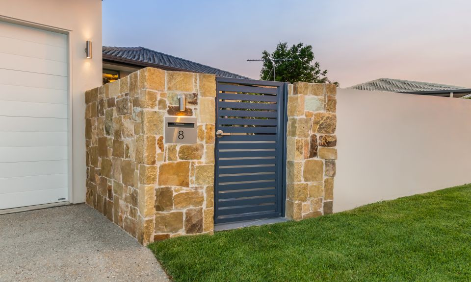 Clancy wall cladding feature to rendered wall fence with Brilliant Vista II fixed spot light above stainless steel letterbox